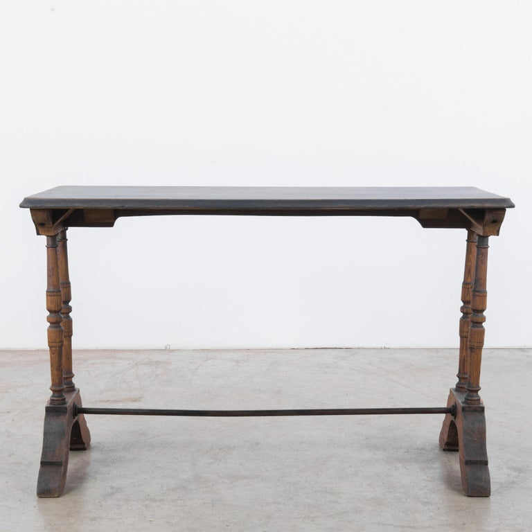 A wooden bistro table from France, circa 1900. A tall, narrow rectangular silhouette; slender turned legs sit atop contoured brackets, joined by a metal strut. The black-painted surface of the tabletop has weathered into a stylish patina, while the