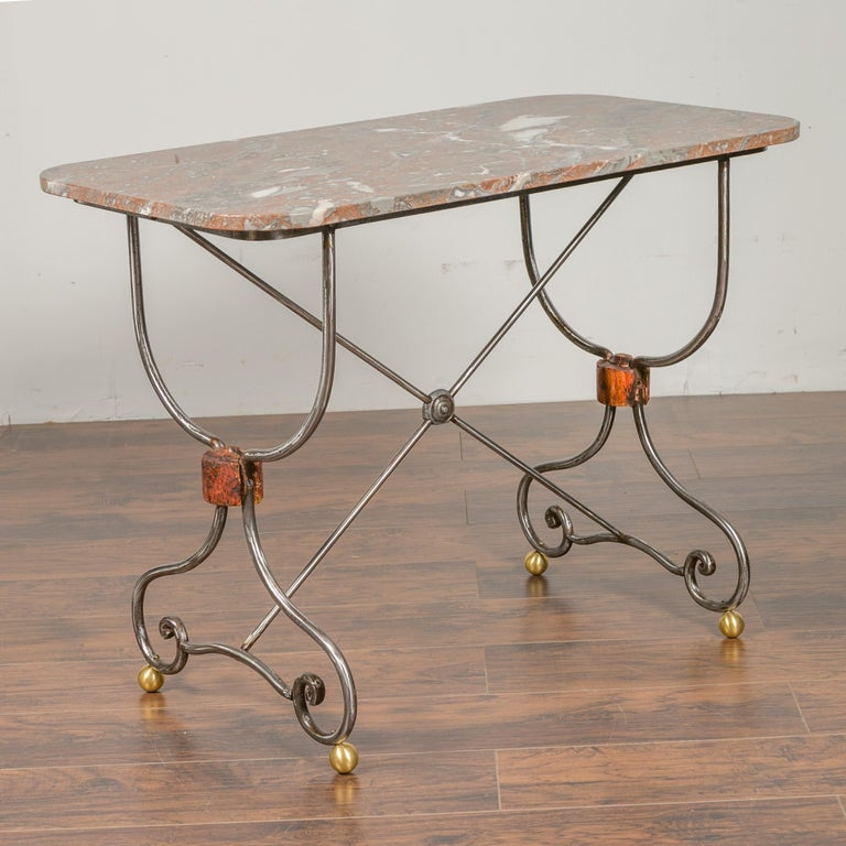 A French steel and brass console table from the early 20th century, with variegated marble top and scrolling feet. We have a twin table available, see item LU836719327362 should you need a pair. They are priced and sold individually. Born in France