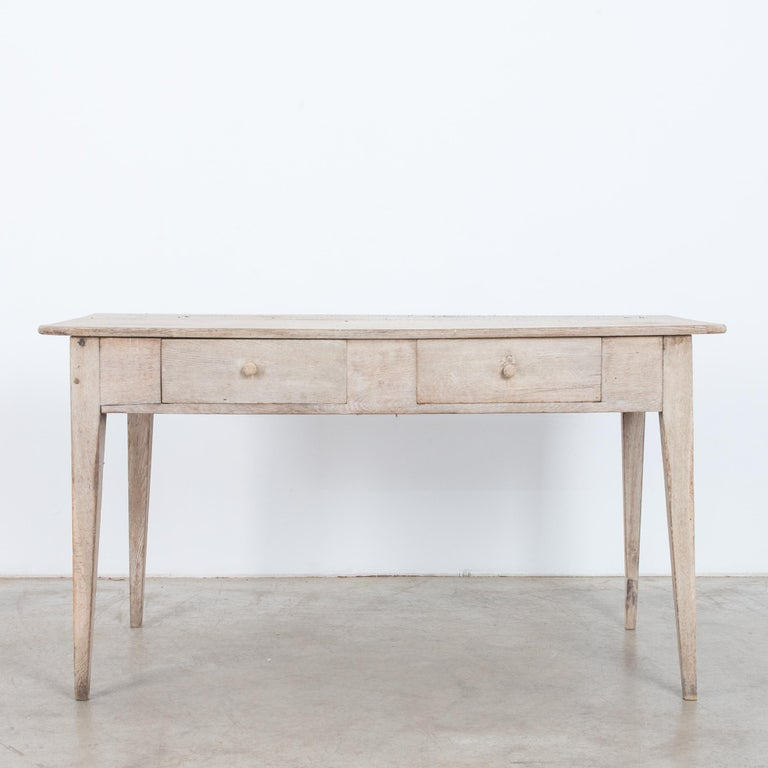 This oak table was made in France, circa 1900. Constructed from clean lines, the tapered, angular legs evoke both simplicity and style. The table houses two drawers and displays a beautifully weathered patina. Perfect as a writing table for your
