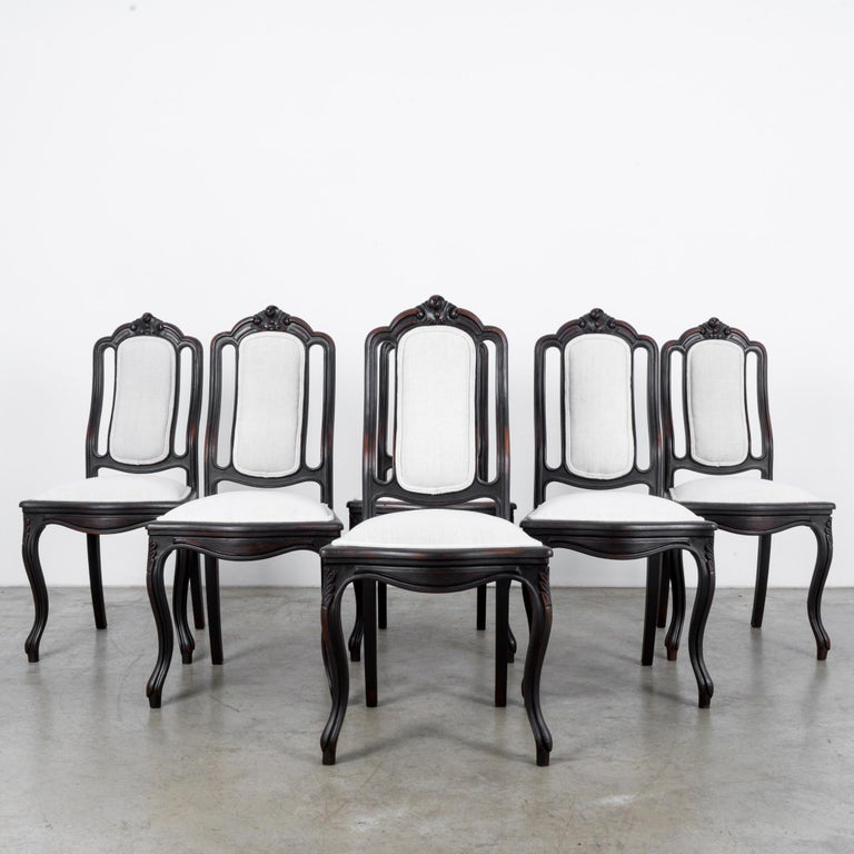 A set of six wooden upholstered dining chairs from France, circa 1900. Rich, dark wood offset by the pale gray upholstery of the seats and backs. Plush pillowing of the seats, the natural curve of the back culminating in a floral crest, and cabriole