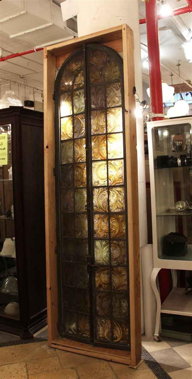 Stained glass arched bronze framed casement window. Secured in a wooden frame. There is a crack in the bottom left portion of the glass. Hand painted floral and leafy detail in amber tones. The dimensions are 98 in. H x 28 in. W, frame 102 in. H x