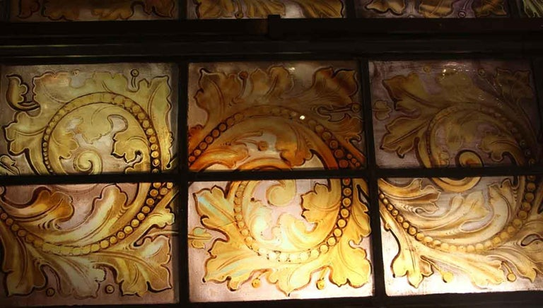 North American 1900s Hand Painted Amber Arched Top Stained Glass Window in Bronze Frame For Sale