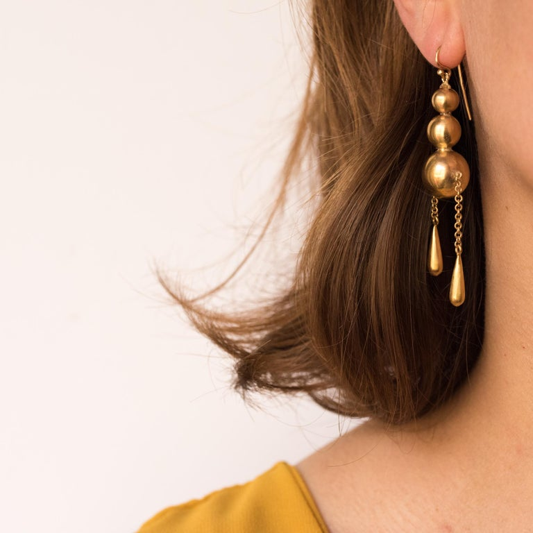 Earrings in 9 karats yellow gold. Large antique earrings, they are made up of a drop of 3 gold pearls, the last and the most important supports in pendent 2 asymetrical chains retaining a motive in drop shape. The hanging system is a