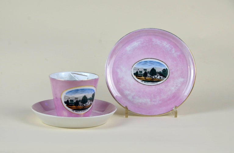 German porcelain souvenir mustache cup finished in an antique pink lustre glaze with two sauces. The cup and the larger saucer are bearing a polychrome image of Llanwrtyd Wells and are marked Made in Germany. Excellent condition with no chips or