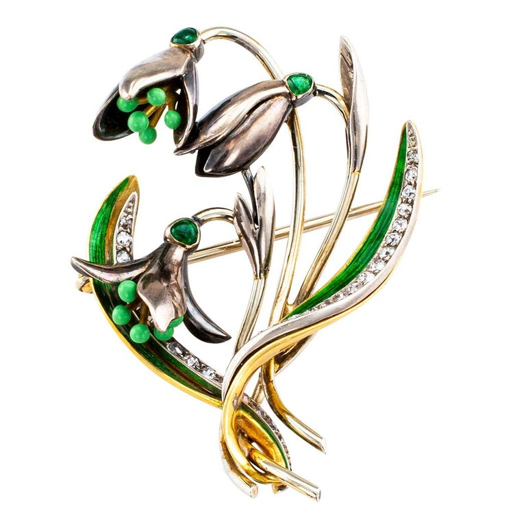 1900s snow drop enamel brooch mounted in gold with diamonds and emeralds. Designed as a trio of snowdrop flowers at varying stages of opening, each capped by a cabochon emerald and terminating in enameled stamens, between a pair of leaves decorated