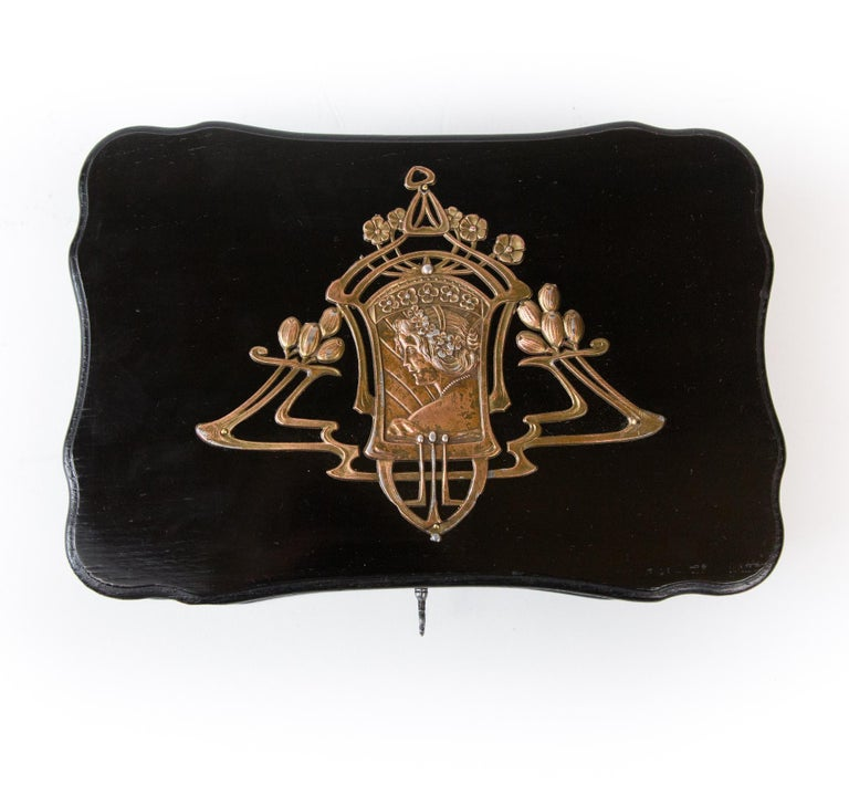 A beautiful Art Nouveau box with openwork application in the Art Nouveau style. Made like a large jewelry brooch. The application pattern is emphasized by ebony black and shine of noble polish.  The wooden casket is an example of Art Nouveau