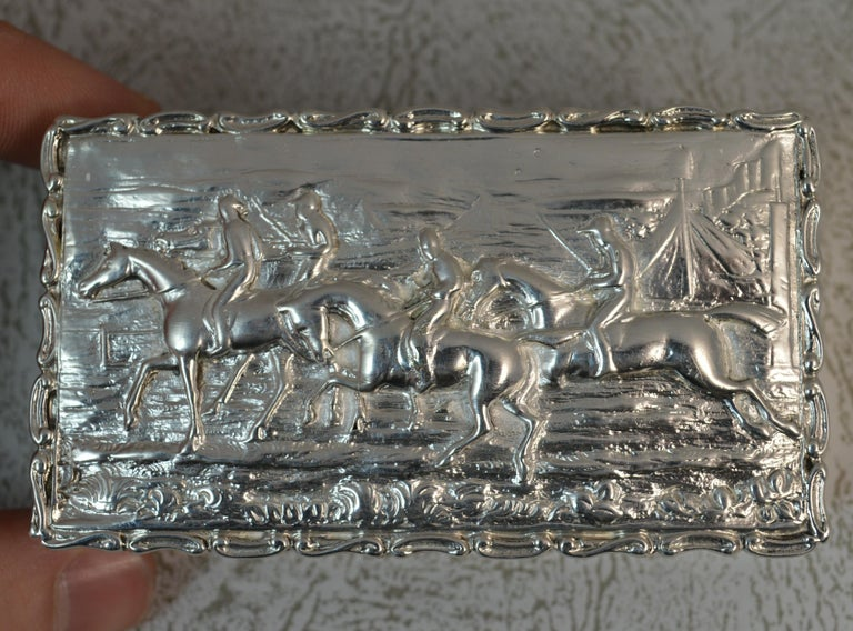 A beautiful solid silver box. Stylish shaped piece of rectangular shape. Scenic hunting design to lid. Pattern to edges. Plain sides.  Hallmarks ; full hallmarks to base Weight ; 92 grams  Size ; 8.4cm x 4.6cm x 2.5cm approx Condition ; Good for