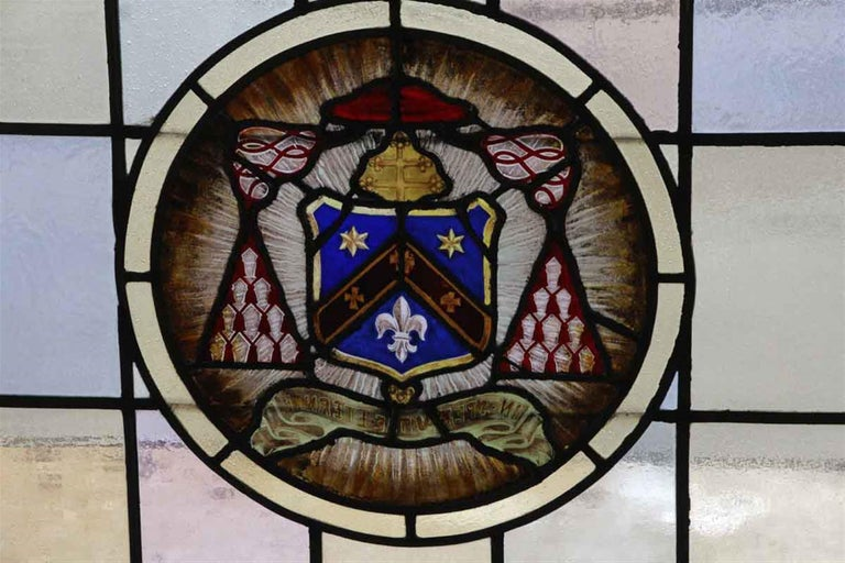 1910 Arts & Crafts wood framed stained glass window with a center shield, fleur de lis and star motif. The glass colors consist of soft hues of blue, green, pink and amber. Some stress cracks. This can be seen at our 400 Gilligan St location in