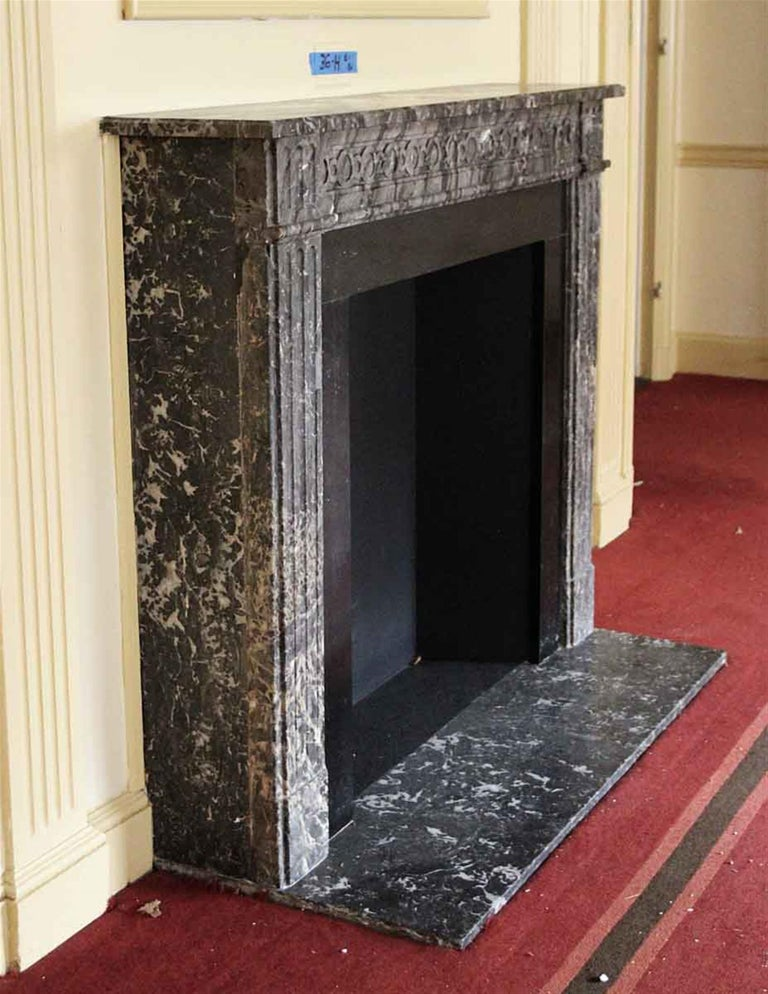 French Regency Louis XVI style gray marble mantel with heavy black and white veining and decorative carved detail on the header. This mantel was one of a group of antique mantels imported from Europe and installed in the NYC Waldorf Astoria hotel in