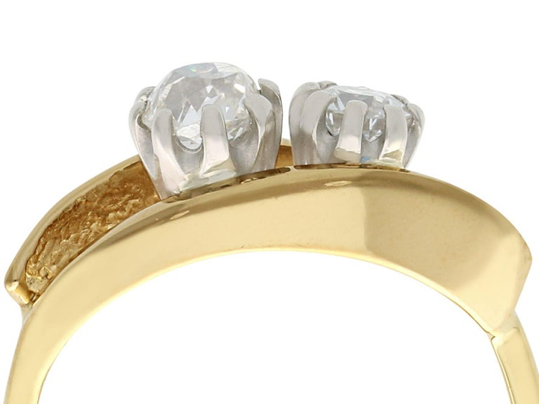 Two antique diamonds displayed in a contemporary 18 karat yellow gold setting; part of our diamond jewelry and estate jewelry collections  This impressive two stone ring has been crafted in 18k yellow gold.  The contemporary pierced decorated