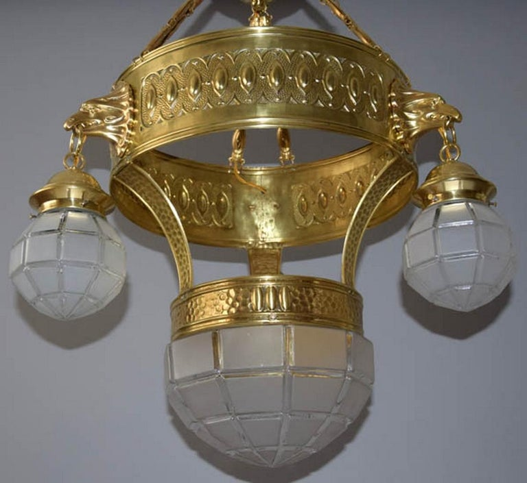 - 3-flamming (similar to eagle heads) - Four lights - Made of polished brass, original matte glass - Carefully cleaned, re-polished and rewired (max. 4x100W, E27) - Diameter of upper circle: 42 cm and diameter of lower glass: 28 cm.