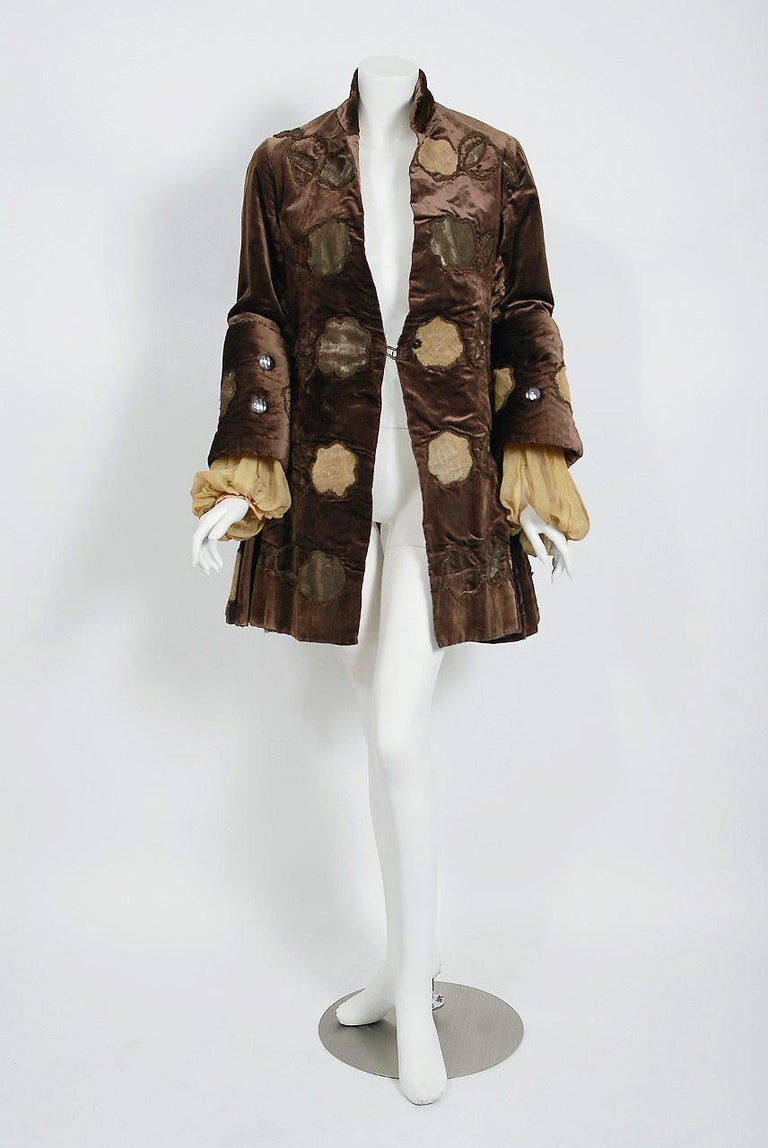 This breathtaking hand-finished Edwardian couture theatrical jacket dates back to the early 1900's. This sensational garment, fashioned in mocha-brown velvet, is lavishly embroidered with metallic gold lamé cording. The highly stylized applique work