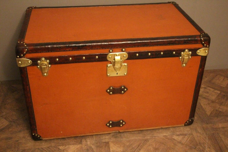 This unusual orange Vuittonite canvas courrier trunk has got all leather trim and handles, all brass stamped LV studs and brass locks. iI has a beautiful original warm orange patina. Its interior is all original too with beige linen, removable