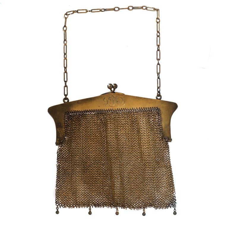 1914 Art Nouveau Mesh Purse - Sterling Silver  Features: Sterling Silver with Gold Wash, Metal has accumulated heavy visible patina  Mesh Body with a Floral Design Frame Link Chain Top Handle and 5-Bead Fringe Bottom  Hinged Opening Inner Frame is