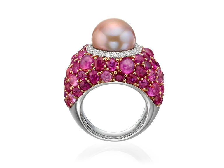 Crafted from 18K rose gold, this cocktail ring features a 13MM freshwater pink pearl at the center surrounded by a halo of white diamonds (totaling 0.51 carats) and a clusters of pink sapphires and rubies (totaling 17.80 carats).  Currently a ring