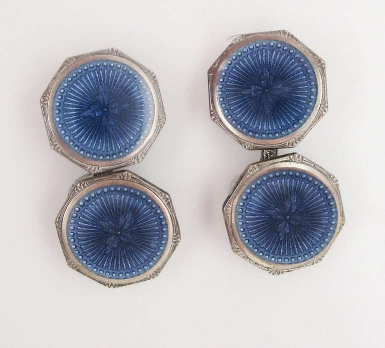 These fantastic octagonal sterling silver cufflinks are signed Krementz have a round guilloche field in a beautiful deep steely blue enamel. The center appears darker, while the rim is lighter, creating a two-tone design. The subtlety of these