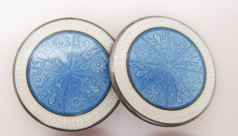 These stunning sterling silver Art Deco cufflinks are from 1915 and feature a delicate floral design in sky blue enamel. The links have a classic round design. The design is framed by a white border with fine, subtle detailing that provides the