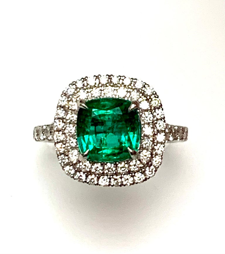1.92 Carat cushion cut Zambian emerald set in 18kw ring , pave set diamonds double halo , diamonds half eay on the shank.