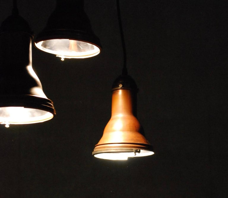 Set of 8 copper pendant lights salvaged from an old theatre in NYC. These copper bodies have a small brass cap holding the socket, with reflective metal interior for maximum effect.