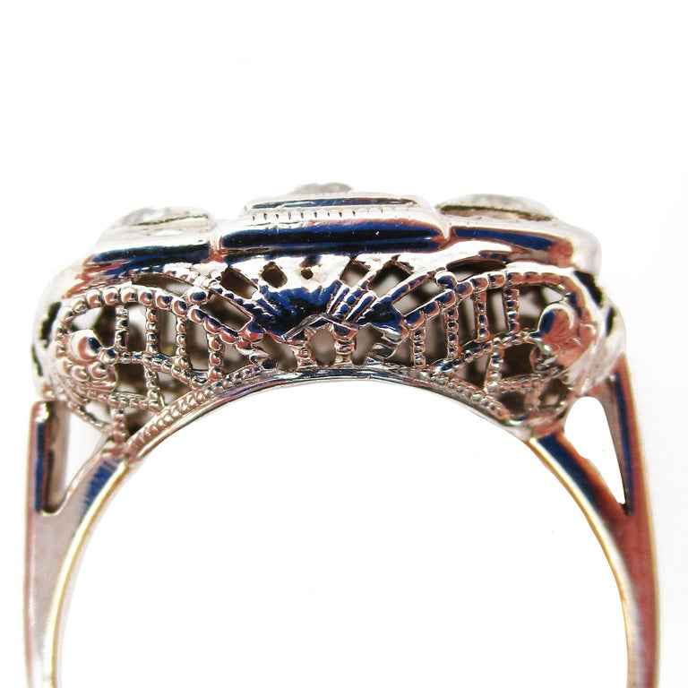 This is an absolutely gorgeous 14 karat white gold filigree engagement ring. It dates back to the 1920s and is overflowing with timeless elegance. The three diamonds are set flat on the head of the ring in a geometric layout. This design keeps the