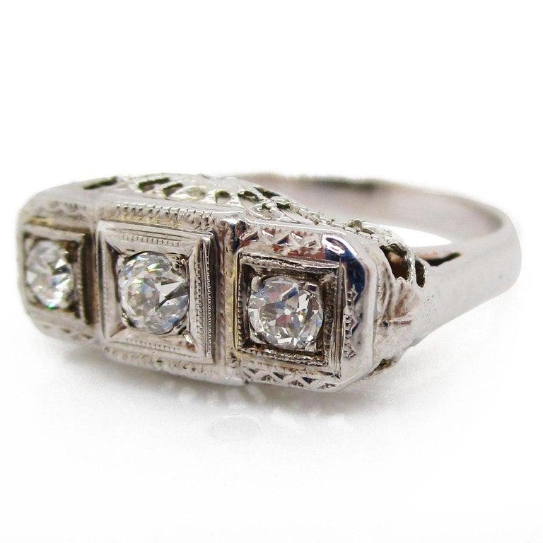 Round Cut 1920s 14 Karat White Gold Filigree Three Diamond Engagement Ring For Sale