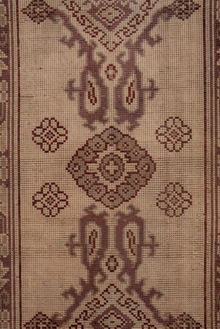 This interwar west Anatolian workshop runner is quite coarse in weave and shows significant overall wear with wefts visible. The creamy ivory field displays a bold Yaprak (Leaf) pattern detailed in green, brown and black. Large and small rosettes