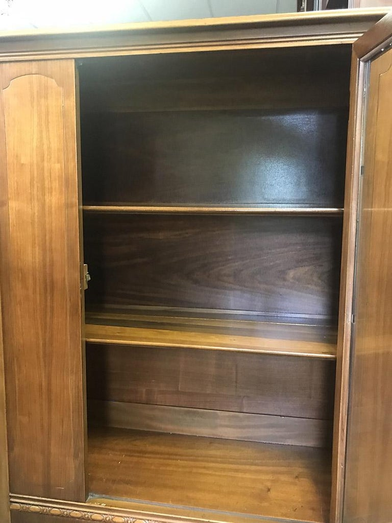 Beautiful restored antique single door bookcase or display cabinet. There are two removable shelves. The glass door is original and so it the hardware. The hardware is antique brass. Simple and elegant detail on either sides of the door and carving