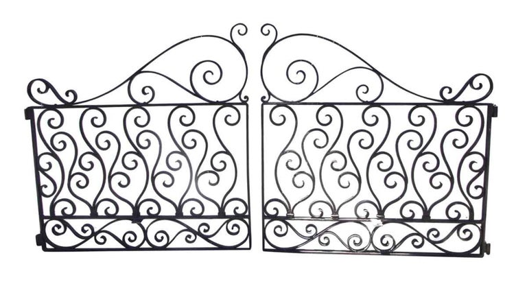 1920s curled swirly detailed two-piece wrought iron driveway gates with a natural black finish. Priced as a pair. This can be seen at our 1800 South Grand Ave location in Downtown LA.