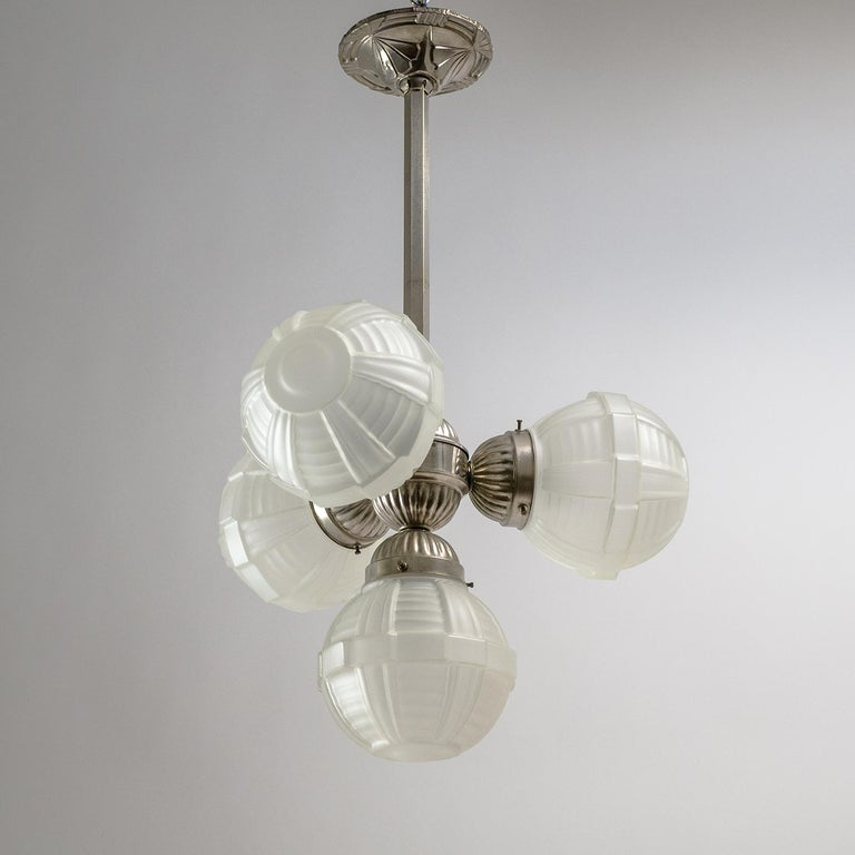 Very fine French Art Deco chandelier from the 1920s with nickelled brass hardware and four geometric textured satin glass globes. A nice mix of geometric patterns without being overly extravagant and in very good original condition with a light