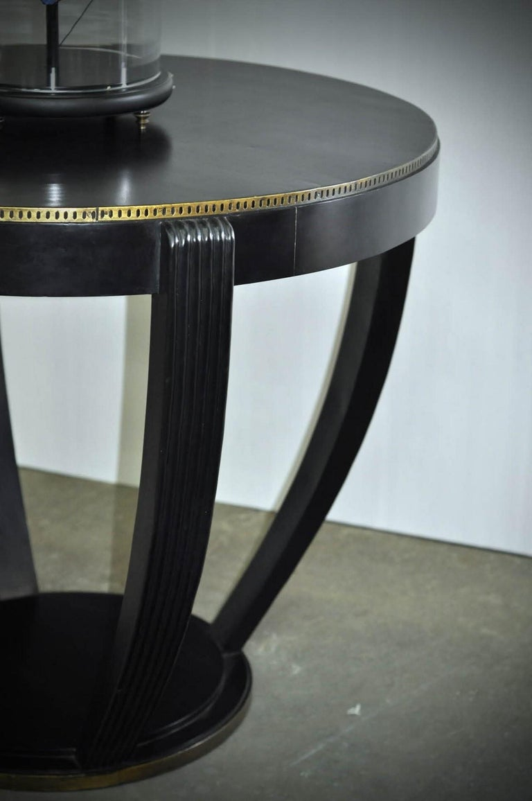 192s Art Deco design round pedestal table consisting of a graphic and geometric black wooden structure adorned with a brass inlay.