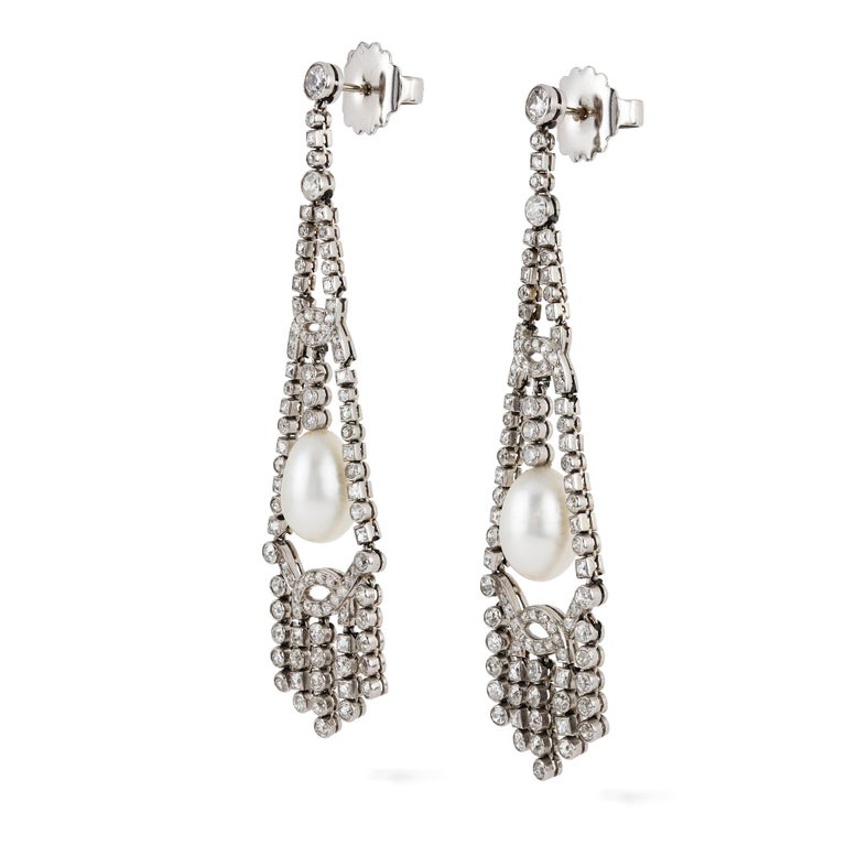 An important pair of Art Deco pearl and diamond fringe drop earrings, the two natural saltwater pearls measuring approximately 8 x 12mm and weighing a total of 10.04 carats, accompanied by Gem & Pearl Laboratory certificate, each suspended within a