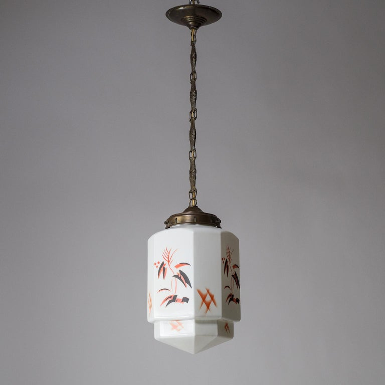 Charming Art Deco pendant from the 1920s. Suspended from an intricately styled brass chain is a hexagonal milk glass diffuser with an abstract floral decor in red and black. Nice original condition with some patina on the dark brass hardware and