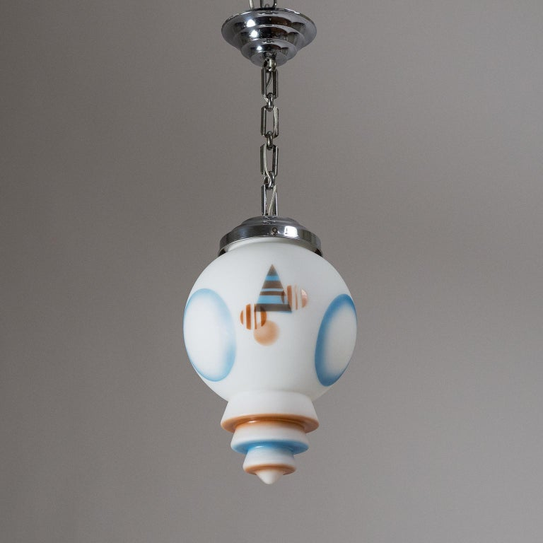 Very unique Art Deco pendant from the 1920s. The 'metropolis' style tiered satin glass diffuser has enameled geometric designs in light blue and dark caramel. The hardware is chromed brass with similarly tiered canopy and glass holder. Very fine
