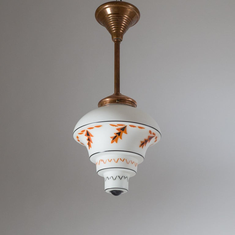 Fantastic pair of Art Deco pendants, circa 1920. Very rare design with copper hardware and tiered satin glass diffusers. The glass has a lovely orange and black enamel decor with stylizes leaves and geometric elements. Very fine original condition.