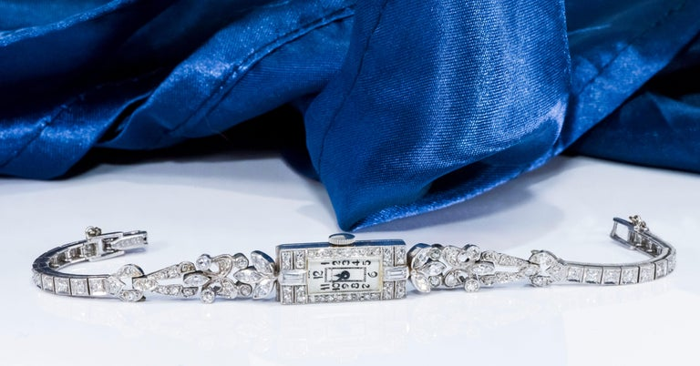 The present Timepiece is an elegant and sophisticated 1920s Art Deco, Platinum Diamond Set Bracelet watch by the world renown firm, Gubelin.  The bracelet is designed with an intricately planned floral motif concept implementing three different