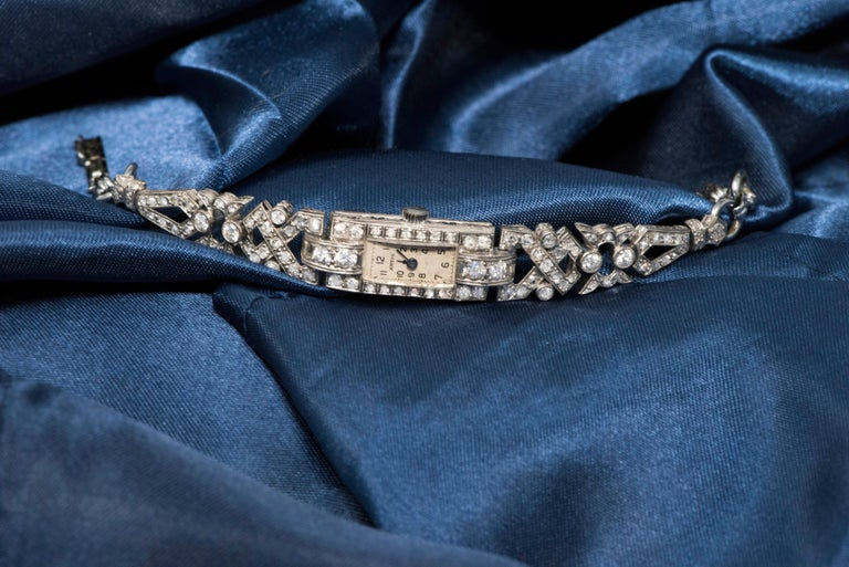The present Timepiece is an elegant and sophisticated 1920s Art Deco, Platinum Diamond Set Egyptian revival motif Bracelet watch.  The bracelet is designed with an intricately planned Egyptian revival motif concept of interwoven triangular and