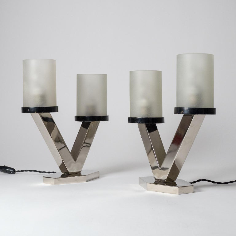 Superb pair of nickelled Art Deco table lamps with frosted glass diffusers, circa 1920. Clean geometric design with a nice asymmetric touch. Nickelled steel base with two asymmetric arms, each holding a lacquered wood disc which supports a thick