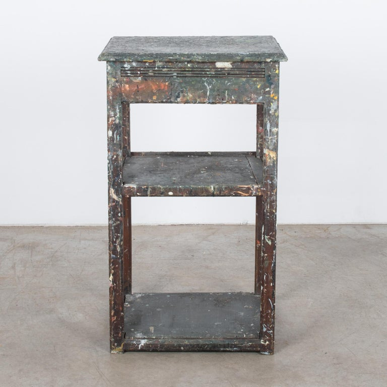A painters table from Belgium, circa 1920. A square painter's box, originally used for storing paints and brushes, sits upon wooden legs. The lid of the painter's box opens on its hinges, sustained with a slender chain. Two lower shelves provide