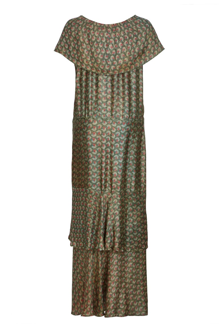 This attractive 1920s lame dress is a pretty but subtle combination of colours, in gold, sage green, pale blue and dusk pink. Unlined, the fabric is light and airy, and the unusual construction of the gown creates a beautiful movement when worn. The