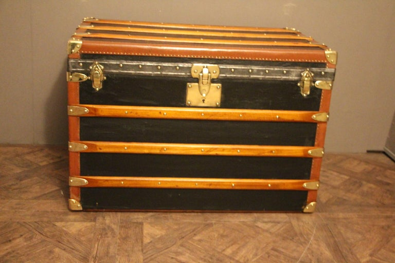This nice steamer trunk features black canvas, honey color lozine trim, large leather side handles and brass corners and locks. Yellow and blue stripes of customization on the sides.. Its main lock as well as its handle latches are marked