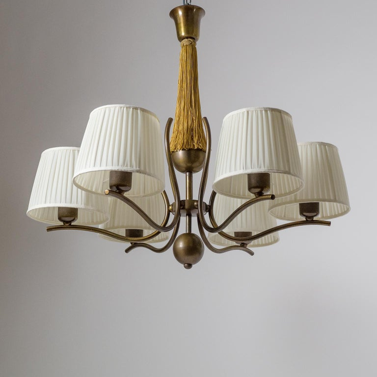 Graceful six-arm bronze chandelier from the 1920s with large pleated fabric shades. Very high quality craftmanship likely produced by J.T. Kalmar. Dark bronze structure with elegantly curved arms and a Fine Minimalist Art Deco design. The stem has