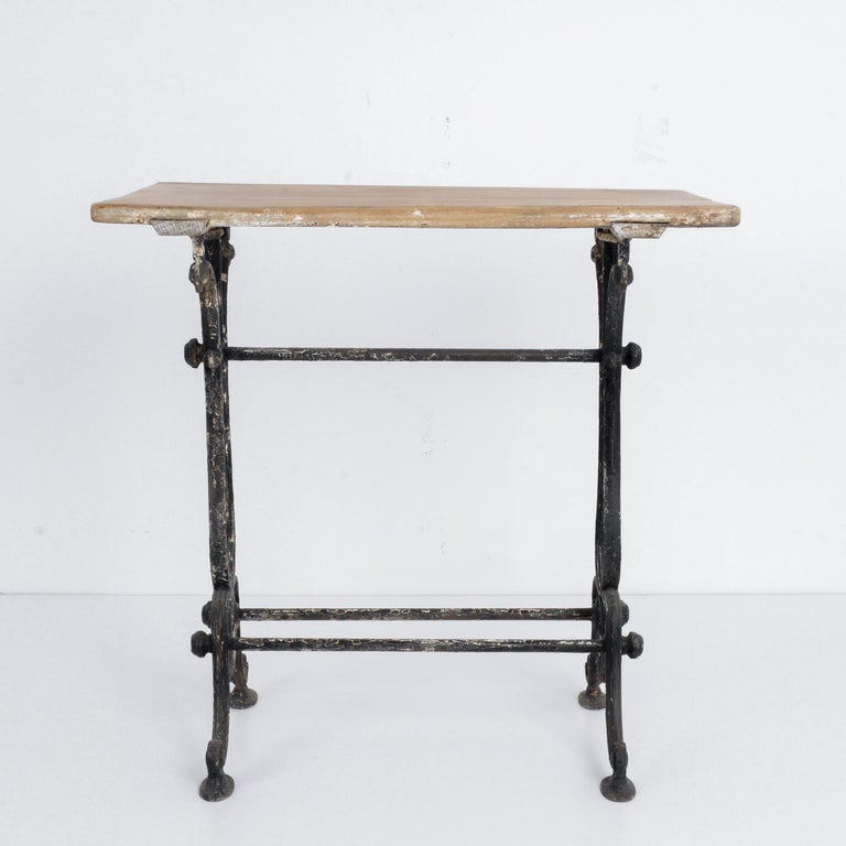 This bistro table with a cast iron frame and wooden tabletop was made in France, circa 1920. The horizontal lines of the table and stretchers highlight the elegant, curvilinear table legs. The table features a timeworn patina, evoking the bustle and