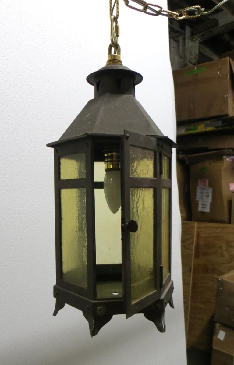 1920s Arts & Crafts style copper lantern with amber colored glass and a single bulb. This light can be seen at our 400 Gilligan Street Scranton Pennsylvania location.