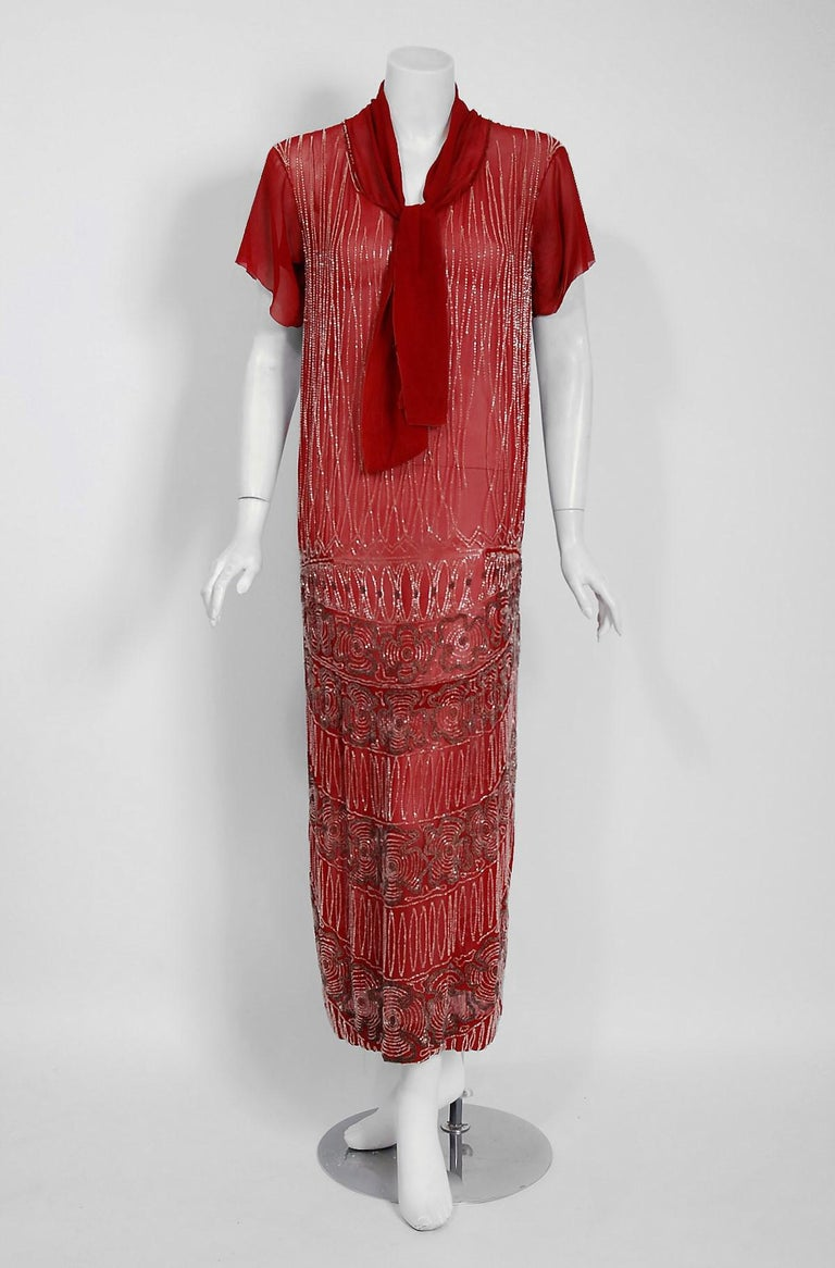 Vibrant flapper dresses from the early 20th century are perennial favorites and this one is a show-stopper! The garment's simple unstructured style is so modern; the fine deco floral beadwork is a treasure trove of needle art. This beauty, fashioned