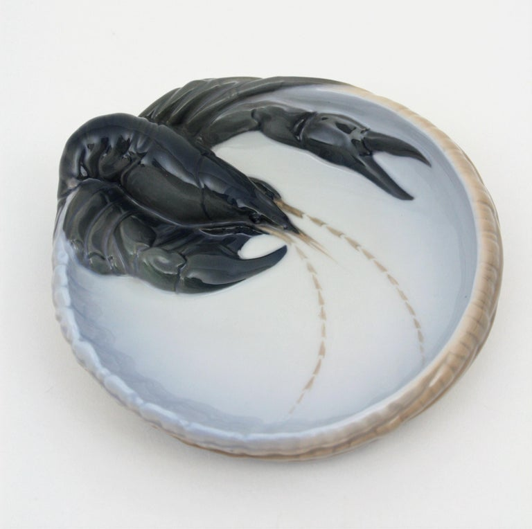 An amazing Royal Copenhagen porcelain basket bowl, dish or ashtray with a highly decorative lobster figurine. This piece is in excellent condition and it is stamped with the manufacture's marks on the back. Useful as jewelry bowl, candy bowl or