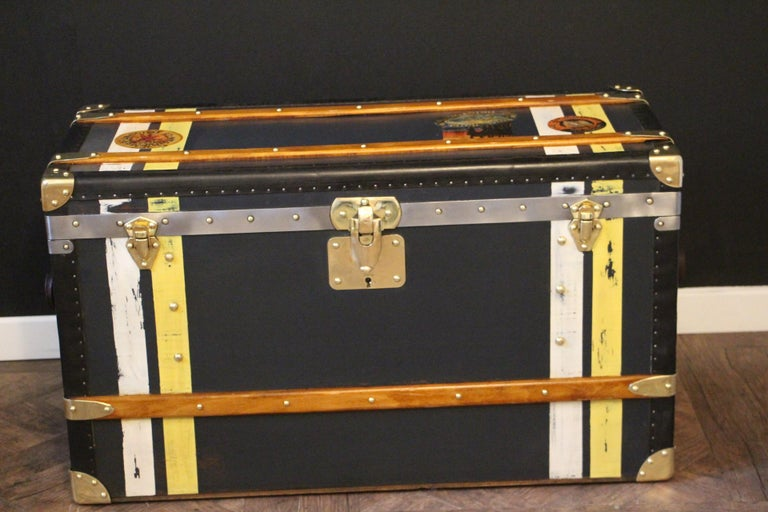 This nice steamer trunk features very unusual dark blue canvas, black lozine trim, large leather side handles and solid brass corners and locks. Its yellow and white painted stripes of customization add personality to this high quality Moynat