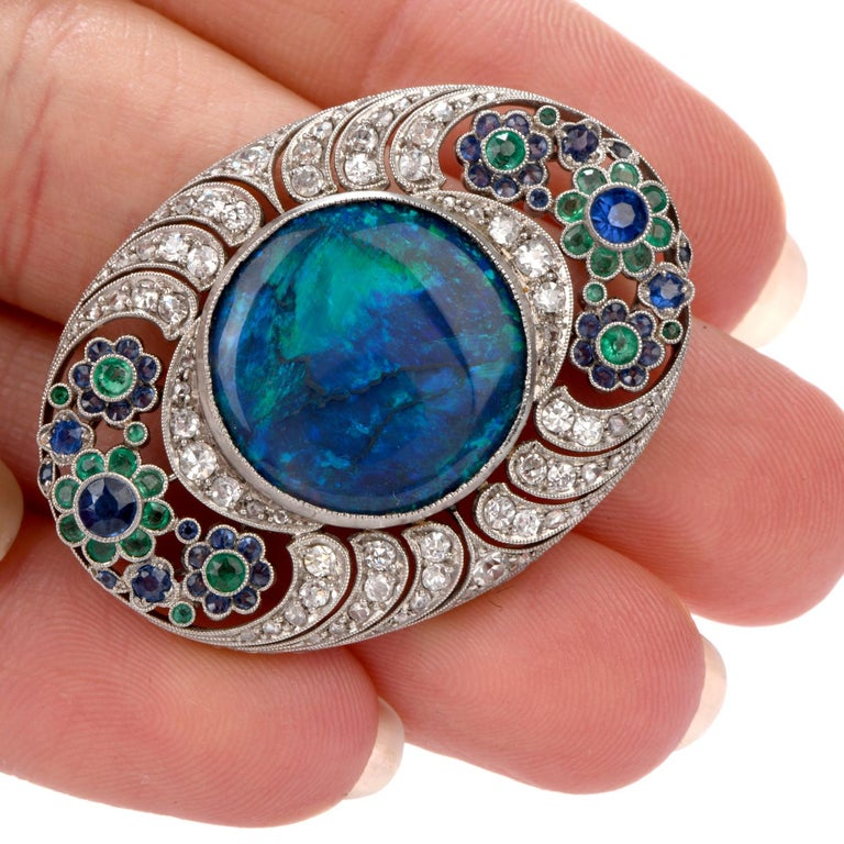 Antique art deco Diamond Opal Sapphire and Emerald Brooch pin inspired in   a stunning floral motif and crafted in Platinum.  Adorning the center of this magnificent brooach is a round shaped   Black Opal gem measuring appx. 17.3mm in diameter