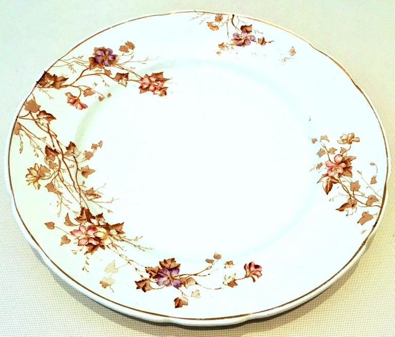 20th century set of eight English ironstone dinner plates by Johnson Brothers. Pattern features a white ground, scalloped edge with 22-karat gold rim and brown with subtle lavender and pink floral vine motif. Each piece is marked on the underside,