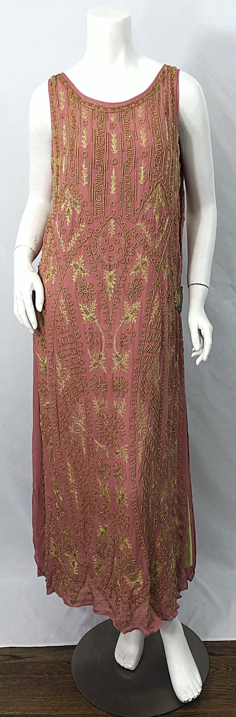 Phenomenal 1920s French couture pink and gold beaded Gatsby style flapper dress ! Features the most beautiful rose colored pink, with gold lame panels at each vent. Rhinestone buckle details at each hip. Simply slips over the head. Hand embroidery