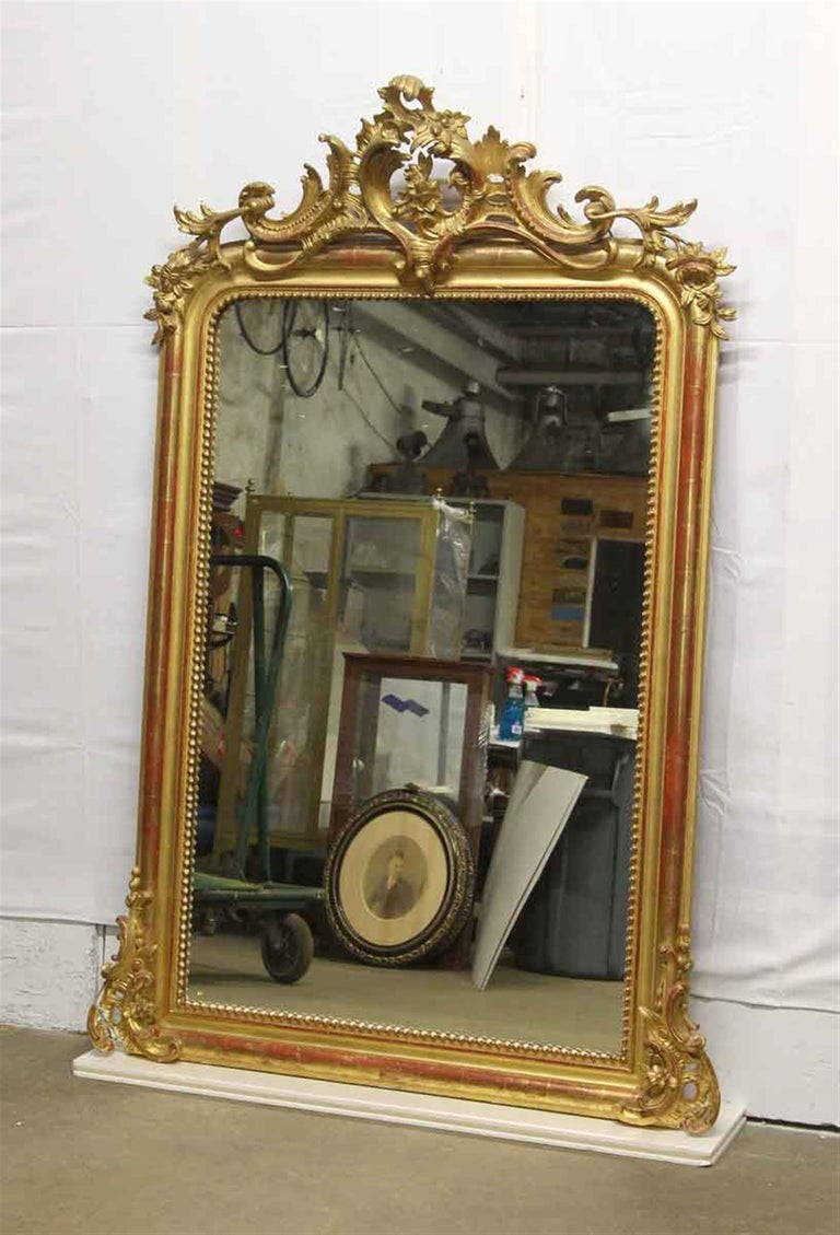 Highly ornate hand carved and gesso 1920s French gilded over mantel mirror. Manufacturer stamp on back. Floral details. Some damages. Please examine the images. This can be seen at our 400 Gilligan St location in Scranton, PA.